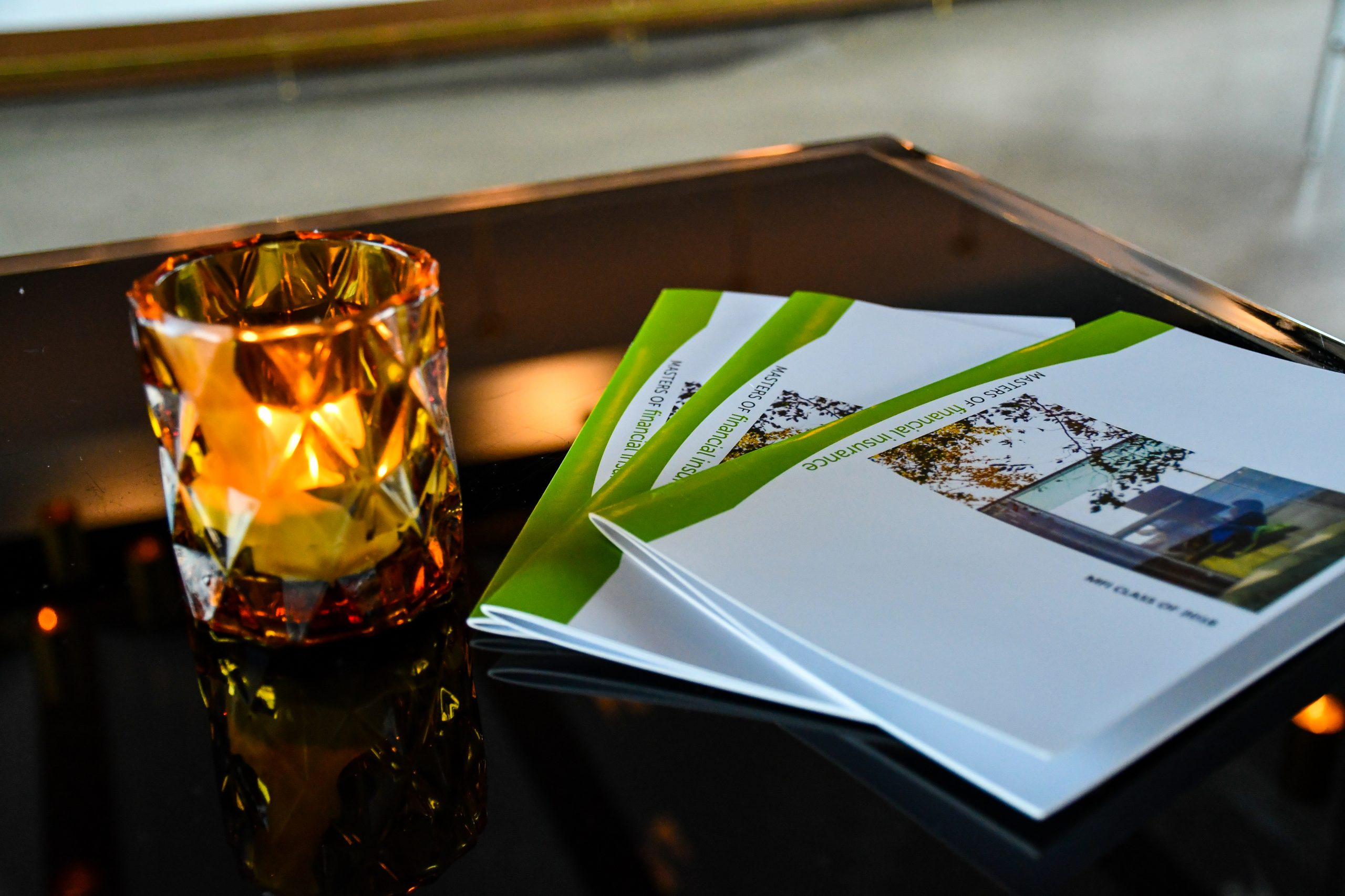 Lighted tea light with white and green booklets on a table